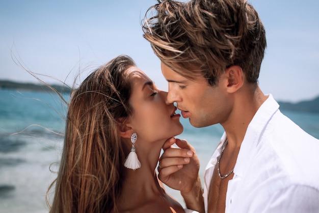 Giovani coppie romantiche in vestiti bianchi che baciano su una spiaggia calda e tropicale. natura luna di miele. phuket. tailandia. avvicinamento