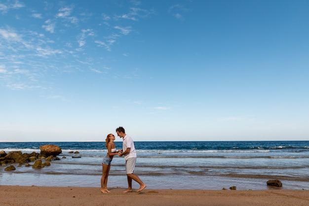 Giovani coppie romantiche sulla spiaggia