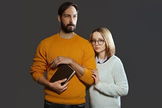 Giovani coppie serie con l'uomo che tiene un libro e una donna con i vetri