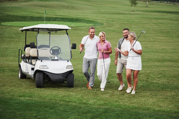 Giovani coppie si preparano a giocare. un gruppo di amici sorridenti venne alla buca su un carrello da golf