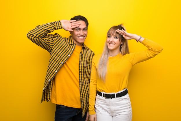 Giovani coppie sopra priorità bassa gialla vibrante che saluta con la mano