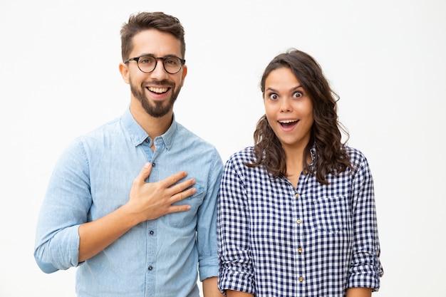 Giovani coppie sorprese che esaminano macchina fotografica