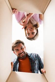 Giovani coppie sorridenti che esaminano la scatola di cartone