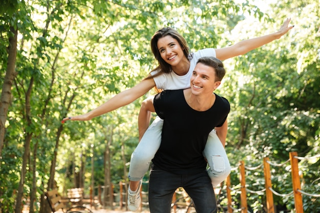 Giovani coppie sorridenti che godono sulle spalle del giro e che ridono