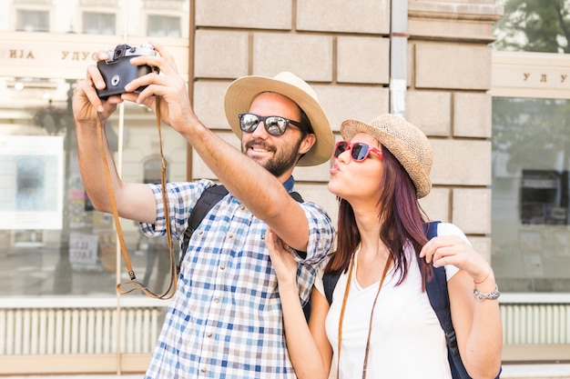 Giovani coppie sorridenti che prendono selfie sulla macchina fotografica