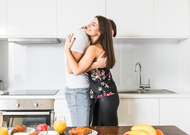 Giovani coppie sorridenti che stanno nell'abbraccio della cucina