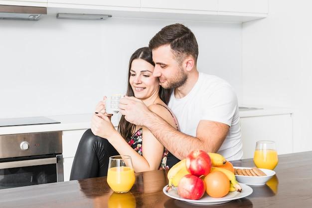 Giovani coppie sorridenti che tintinnano la tazza di caffè mentre mangiando la prima colazione