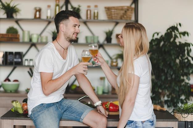 Giovani coppie sorridenti che tostano i vetri di birra nella cucina