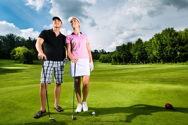 Giovani coppie sportive che giocano a golf su un corso