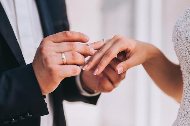 Giovani coppie sposate che si tengono per mano, giorno delle nozze di cerimonia