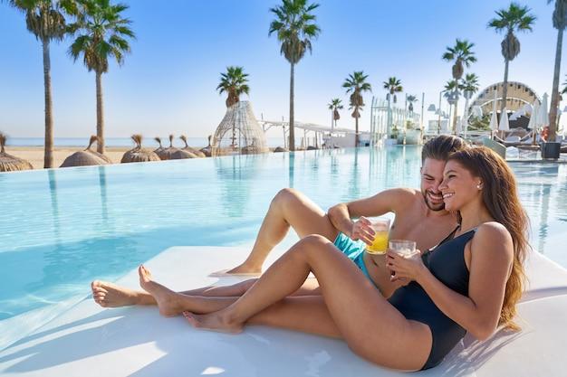 Giovani coppie sull'amaca dello stagno al beach resort