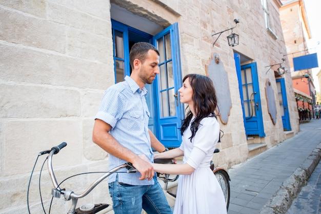 Giovani coppie sulla bicicletta in tandem alla città della via