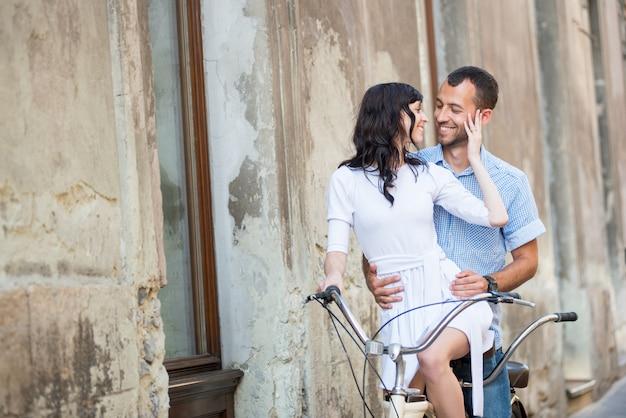 Giovani coppie sulla retro bicicletta in tandem alla città via