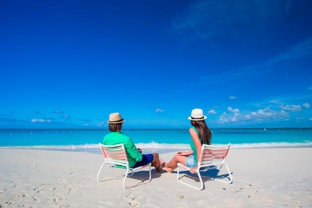 Giovani coppie sulla spiaggia bianca alle vacanze estive