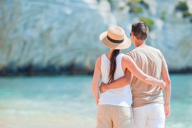 Giovani coppie sulla spiaggia bianca durante le vacanze estive