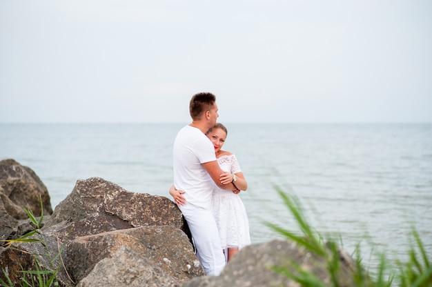 Giovani coppie sulle rocce nel mare