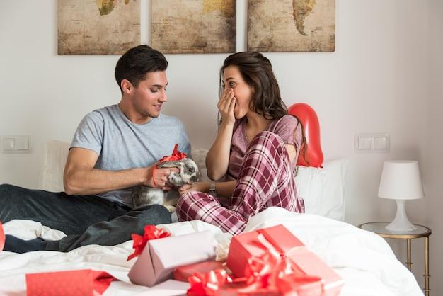 Giovani coppie sveglie che danno un coniglietto come regalo