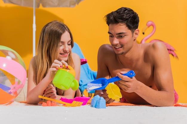 Giovani coppie sveglie che giocano i giocattoli per la sabbiera in studio