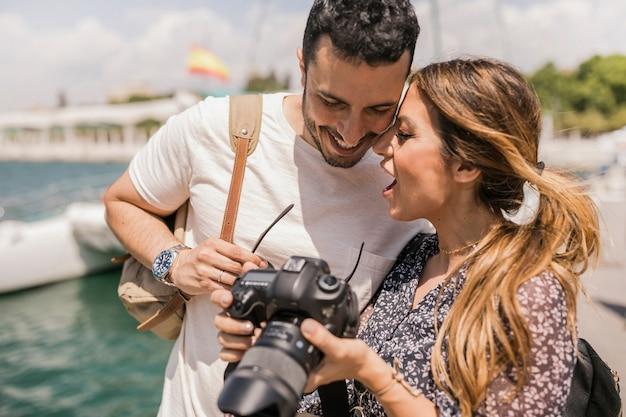 Giovani coppie turistiche divertenti con la macchina fotografica del legamento