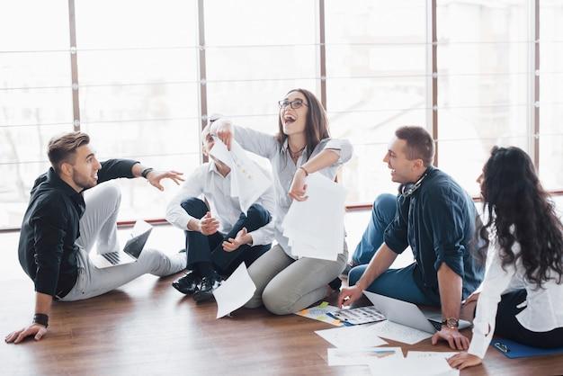 Giovani creativi in ufficio moderno. gruppo di giovani imprenditori stanno lavorando insieme al computer portatile. liberi professionisti seduti sul pavimento. cooperazione aziendale. concetto di lavoro di squadra