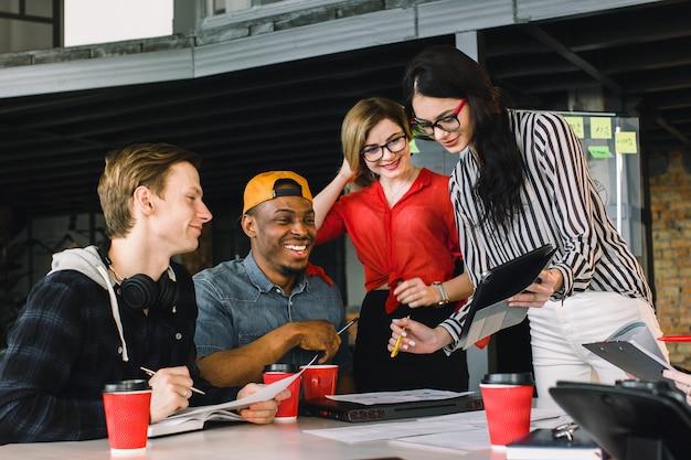 Giovani creativi multirazziali in ufficio moderno. gruppo di giovani imprenditori stanno lavorando insieme a laptop, tablet, smartphone, notebook. squadra hipster di successo nel coworking.