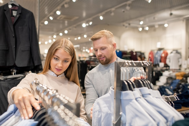 Giovani date che guardano attraverso la collezione di camicie appese agli scaffali mentre visitano un grande centro commerciale a piacere