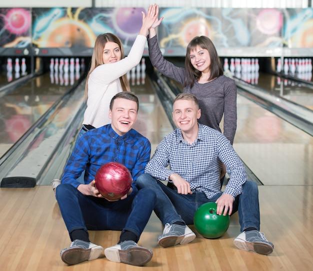 Giovani divertenti che sorridono alla macchina fotografica che gioca bowling.
