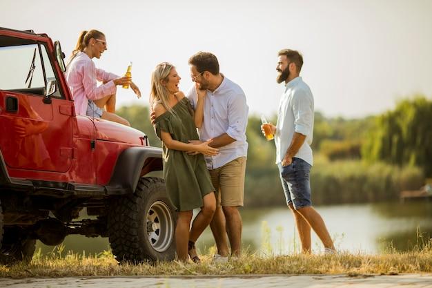 Giovani divertirsi in auto convertibile dal fiume