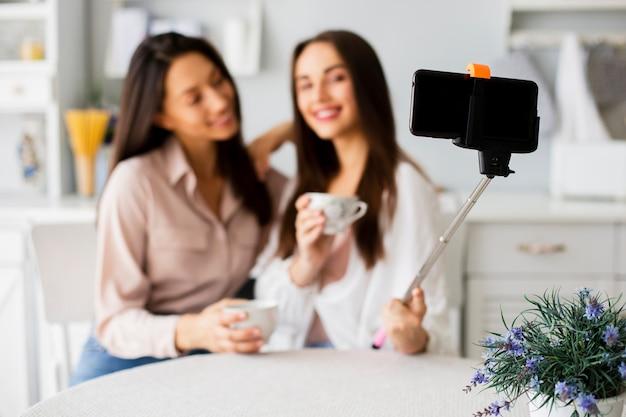 Giovani donne a casa che prendono selfie