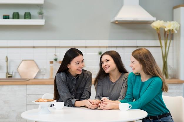 Giovani donne adorabili che mangiano caffè a casa