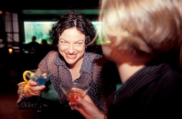 Giovani donne al bar con bevande, sorridendo
