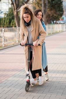 Giovani donne alla moda che guidano motorino elettrico