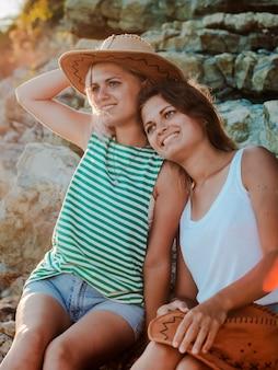 Giovani donne allegre in cappelli hipsters su una roccia sulla costa del mare.