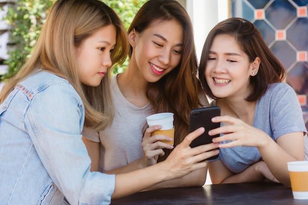 Giovani donne asiatiche allegre che si siedono nel caffè bevente del caffè con gli amici e che parlano insieme