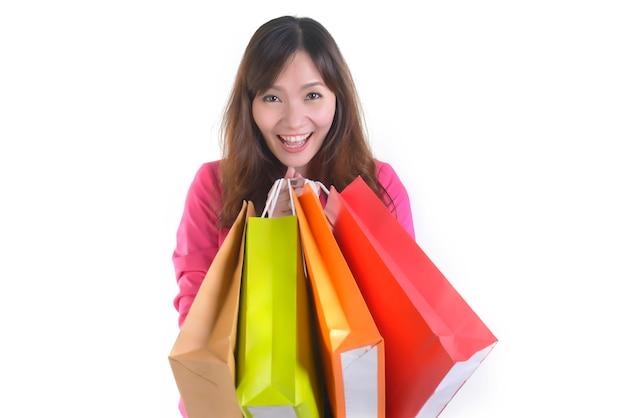 Giovani donne asiatiche d'acquisto che tengono i sacchetti della spesa.