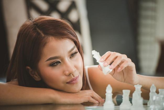 Giovani donne attraenti che progettano nel salone a casa con il gioco della scacchiera