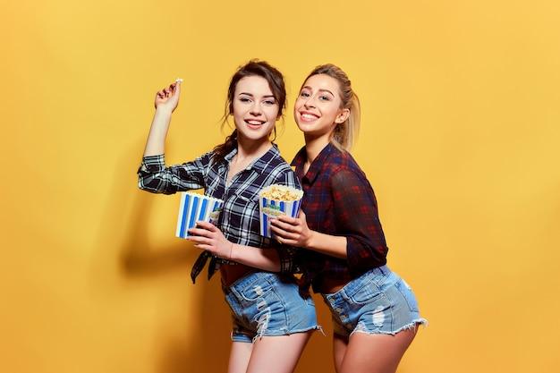 Giovani donne attraenti con popcorn