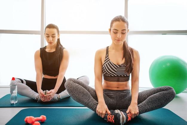 Giovani donne calme e concentrate siedono nella posizione del loto e tengono i piedi uniti.