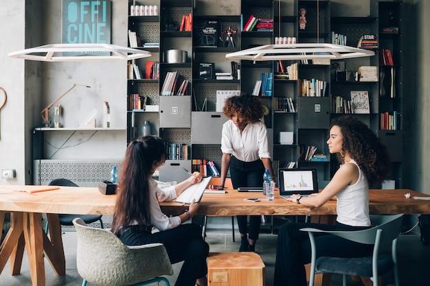 Giovani donne che discutono il progetto nello spazio coworking