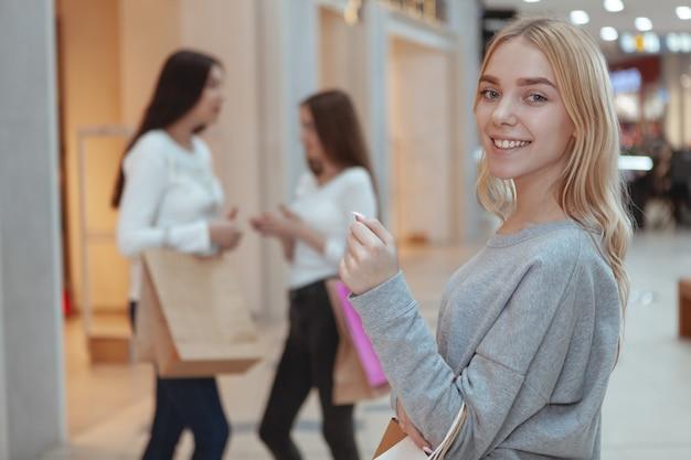 Giovani donne che godono della compera insieme al centro commerciale