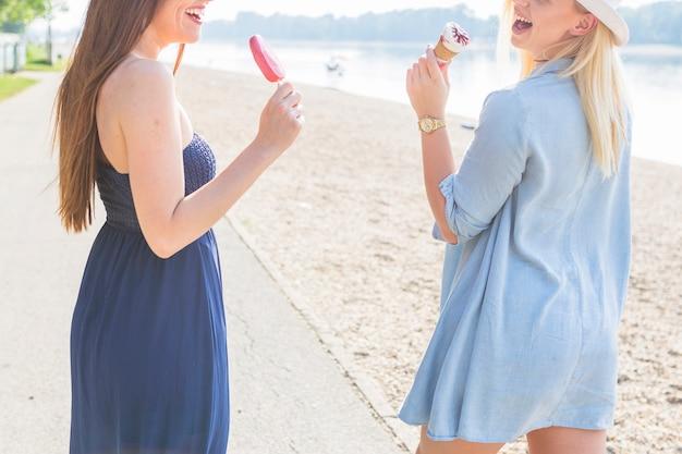 Giovani donne che godono il ghiacciolo e cono gelato in spiaggia