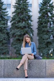 Giovani donne che lavorano al computer portatile nella piazza della città
