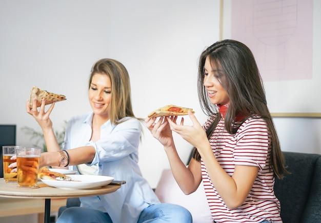 Giovani donne che mangiano la pizza degli alimenti a rapida preparazione e che bevono birra a casa