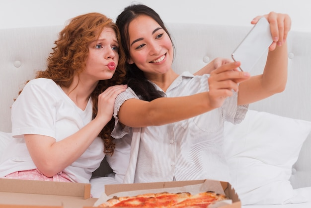 Giovani donne che prendono selfie mentre mangiano pizza
