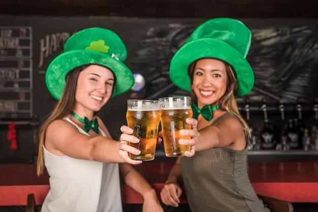 Giovani donne che ridono in cappelli di saint patricks mostrando bicchieri di drink al bancone del bar