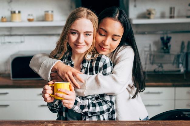 Giovani donne che si abbracciano in cucina