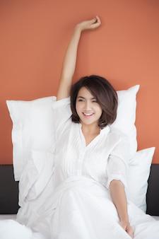 Giovani donne che svegliano che allunga di mattina sul letto con il fronte di sorriso felice