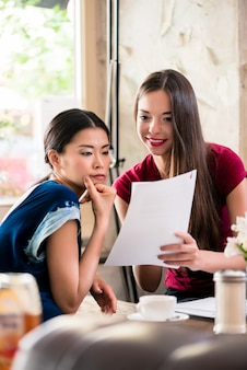 Giovani donne che tengono gli archivi in una caffetteria