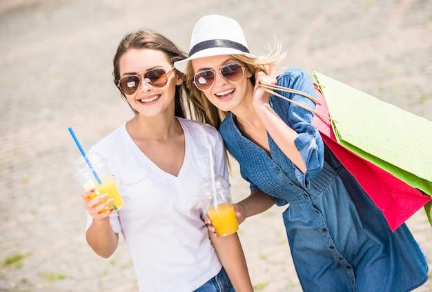 Giovani donne che tengono i sacchetti della spesa e vetri di succo.