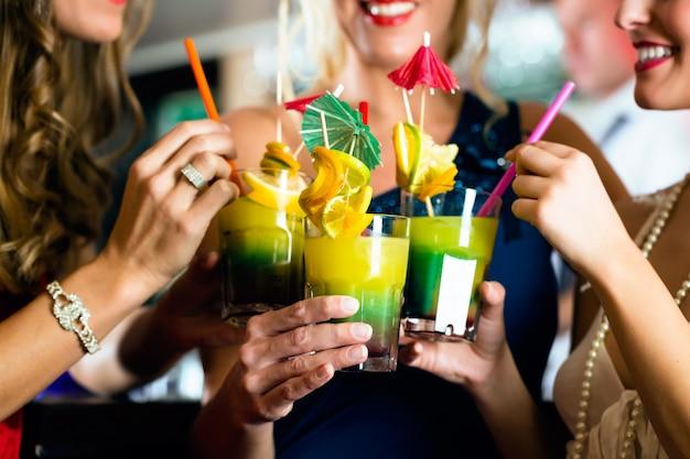 Giovani donne con cocktail nel bar o club